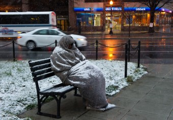 person wrapped in blanket on bench in snow